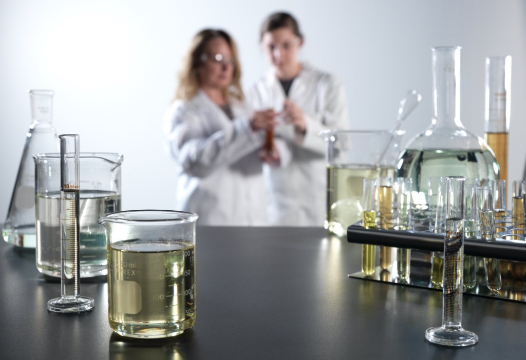 An image of quality control specialist and a lab engineer examining a formula of Synova Release Agents supports Bundy Baking Solutions press release for the new Synova brand.